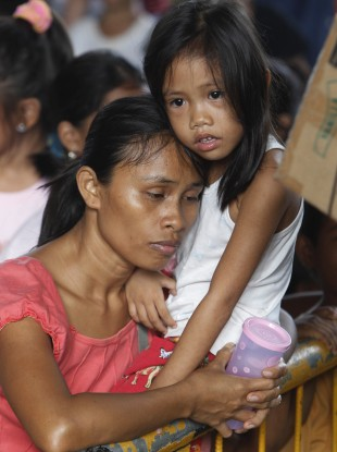 Residents queue up for relief supplies being distributed at an evacuation centre yesterday