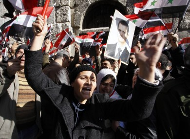 Mourners wave Syrian flags and a photo of President Bashar Assad as they chant slogans at a mass funeral for 44 people killed in suicide bombings earlier this week.
