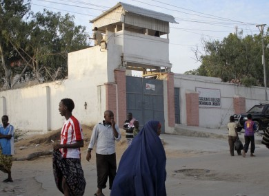 Residents walk outside of the Medecins Sans Frontieres (Doctors without Borders) compound in Mogadishu, Somalia