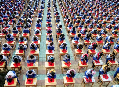 Students of No 3 Middle School in Tancheng, China practice their handwriting for the upcoming Year of the Dragon
