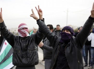 Masked Syrian refugees make victory signs at a protest in front of the Syrian embassy while chanting slogans against President Bashar Assad in Amman, Jordan