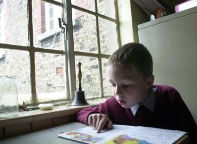 A 6-year-old student reading beside a broken window in a school in Phibsboro, Dublin (File photo)