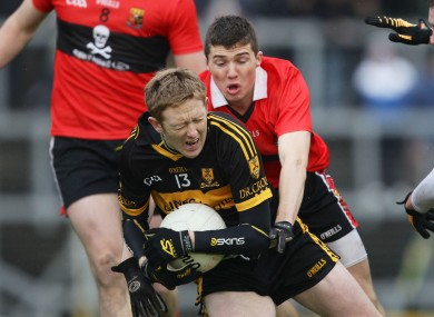 Dr Crokes' Colm Cooper is wrapped up by UCC's Tom Clancy