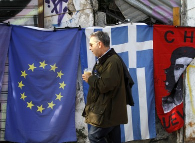 A pedestrian passes by flags for sale in Athens last year