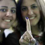 Egyptian women show their inked fingers after voting in Cairo, Egypt. Record numbers of people turn out to cast their votes. (AP Photo/Amr Nabil)
