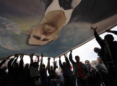 Bashar Assad supporters wave a banner with his likeness in Damascus last week.