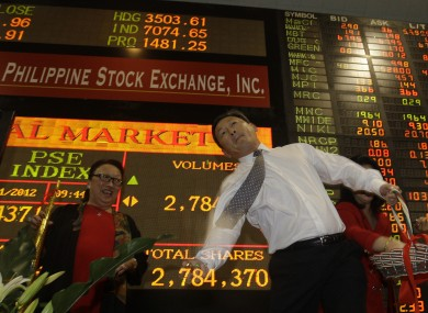 Philippine Stock Exchange director Alejandro Yu throws chocolate coins at the start of trading to mark the first trading day of 2012.