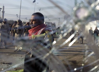 Iraqi security forces and civilians seen through smashed glass after an explosion in Baghdad earlier this month.