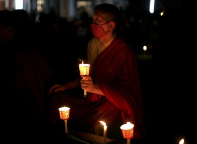 A Tibetan Buddhist monk holds a candle during a candlelit vigil for Tibetans who self-immolated in Tibet, in Bodh Gaya, Bihar state, India, Sunday, Jan. 8, 2012