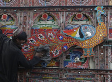 A truck driver cleans his vehicle in Lahore, Pakistan.