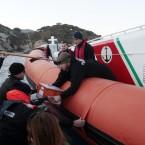 Italian Coast Guard personnel pass on the black box from the Costa Concordia on Saturday. (AP Photo/Gregorio Borgia/PA Images)