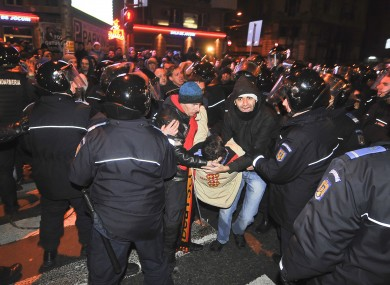 Protesters evacuate an injured person during clashes with Romanian riot police in University Square in Bucharest, Romania, early Sunday morning, Jan. 15