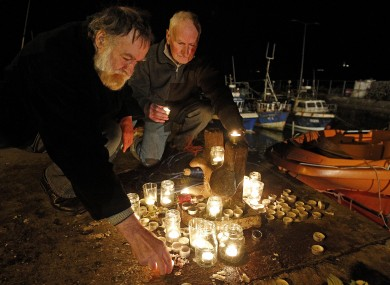 Gus Dempsey (left) and George Webb light candles at a memorial in Union Hall for the five missing men off the coast.