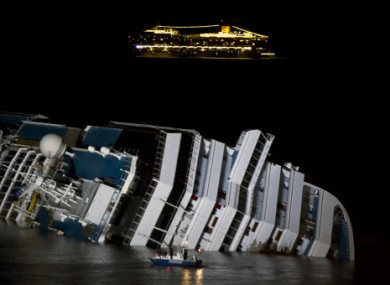 The cruise ship Costa Serena passes its sister ship Costa Concordia lying off the Italian coast.