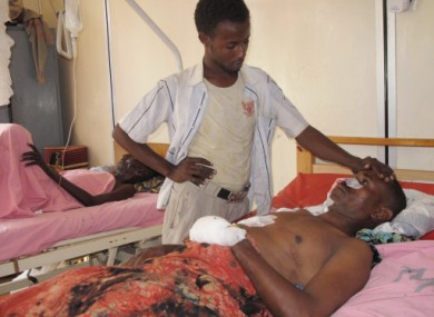 An injured man is comforted by a relative after today's explosion in Mogadishu.