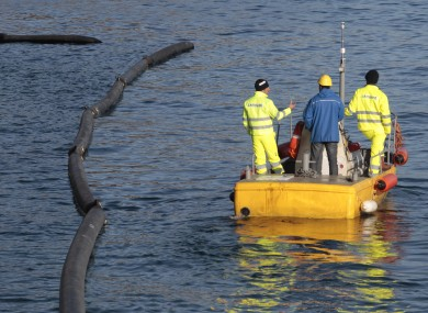 Workers inspect the booms designed to prevent oil contamination