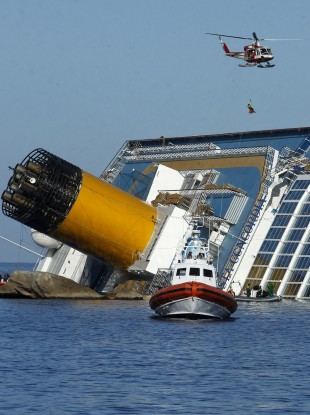 A rescue worker being lowered onto the ship from a helicopter today