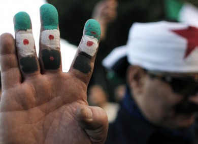 An anti-Syrian regime protester colors his fingers with the revolutionary flag colors during a protest outside the Arab League headquarters in Cairo, Egypt, last Sunday