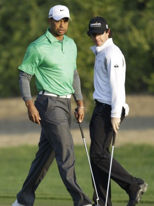 Tiger Woods and Rory McIlroy examine their putts on the 10th green in Abu Dhabi this morning.