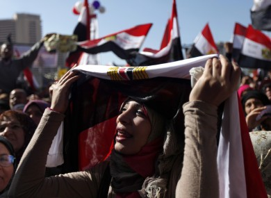 A female Egyptian protester chants slogans and holds a national flag at a rally to mark the first anniversary of the