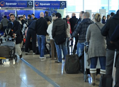 Passengers wait at a Spanair desk at Barcelona airport yesterday