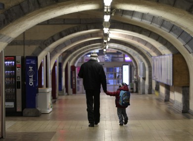 A man and a child walk through an empty hallway of Belgium's second busiest train station in Ghent this morning. The country has been effectively shut down by a general strike.