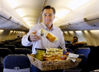 Mitt Romney throws bags of potato chips at reporters travelling with his campaign in Florida yesterday.