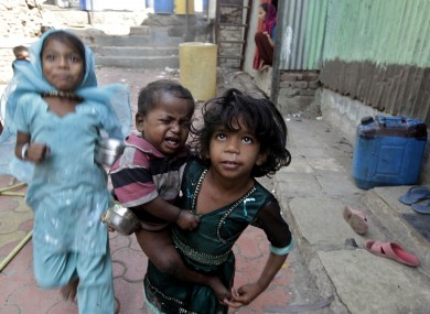 A girl holds a malnourished child outside the Apanalay center that works with malnourished children in Mumbai, India (File photo)