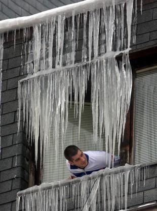 A man views icicles on a window in Uzice 200 kilometers (125 miles) southwest of Belgrade, Serbia, Thursday, Feb. 2, 2012.