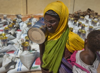File: A woman carries a child and a tin of vegetable oil she just received at a food distribution center in Mogadishu, Somalia.