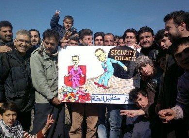 Anti-Assad rotesters pose with a banner depicting Assad with Vladimir Putin and bearing the words