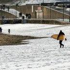 A surfer walks to the sea across the beach at Scarborough, Yorkshire, following heavy snow across the UK overnight. (John Giles/PA Wire)