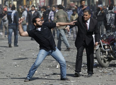 A man urges a protester to stop throwing stones at security forces during today's clashes in Cairo.