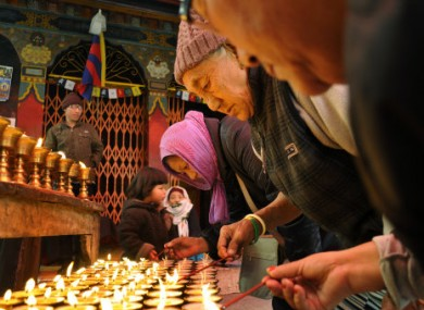Tibetan Buddhist exiles offer prayers and light candles in solidarity with Tibetans protesting against Chinese rule.