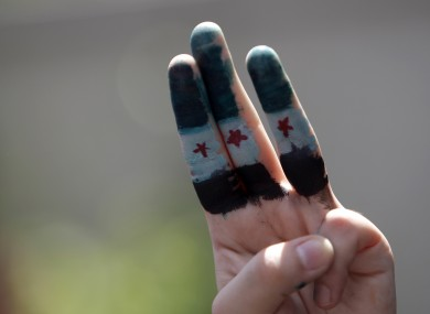 A Syrian living in Malaysia with her fingers painted with Syrian flag takes part in a protest rally to condemn the killing by Syrian regime.