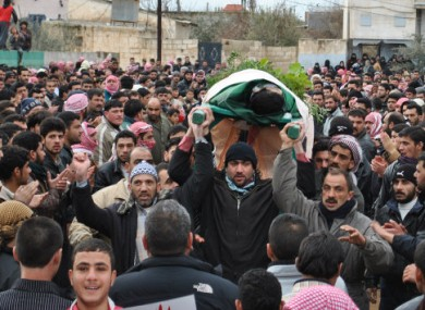 Anti-regime protesters in Syria cary the body of a man they claim was killed by government forces in Rastan, Homs.