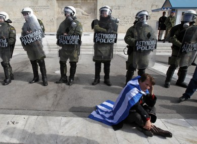 A protester wearing a Greek flag sits in front of riot police during a rally outside the Greek Parliament yesterday.