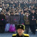 North Koreans walk towards a stand at Kim Il Sung Square in Pyongyang to lay flowers beneath a large portrait of the late leader. (AP Photo/David Guttenfelder/PA Images)