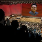 North Koreans applaud as a large screen shows a portrait of the late North Korean leader Kim Jong Il. (AP Photo/David Guttenfelder/PA Images)