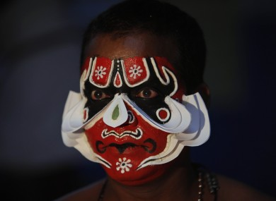 An Indian Kathakali dancer prepares for a performance in Hyderabad today.