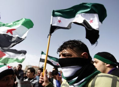 Syrians take part in a protest against Syrian President Bashar al-Assad in front of the Syrian embassy in Amman, Jordan