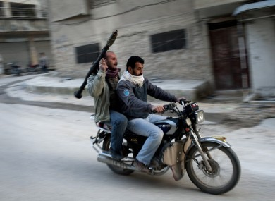 Supporters of the Free Syrian Army ride a motorcycle with a rocket-propelled grenade in Kafar Taharim, Syria