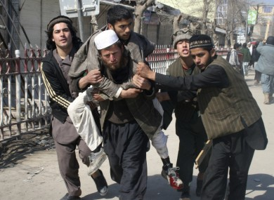 Afghans carry a wounded man during an anti-US demonstration in Kunduz, north of Kabul, Afghanistan