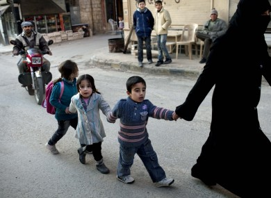 A woman walks with children in Kafar Taharim, north Syria on Saturday. The town is controlled by the opposition Free Syrian Army.