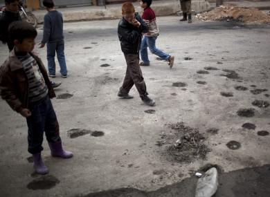 Syrian boys looking at damage caused after a clash between the Free Syrian Army and President Assad's forces
