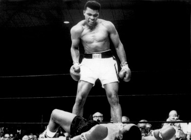 Champion Muhammad Ali stands over Sonny Liston and taunts him to get up after knocking him down.
