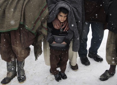 File photo: Internally displaced Afghans wait for blankets and winter clothing at a camp in Kabul, 20 February.