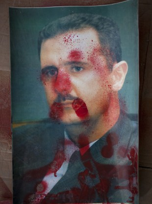 A portrait of Syrian President Bashar Al-Assad defaced with red paint is sown during an anti-government demonstration in the outskirts of Idlib in the north of the country