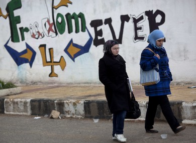 Women walk past graffiti on the outskirts of Idlib in north Syria
