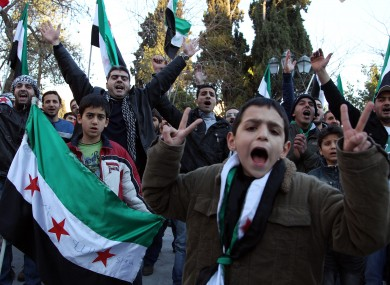 Syrian nationals who live in Greece shout slogans and wave the revolutionary Syrian flag during a protest in Athens today.